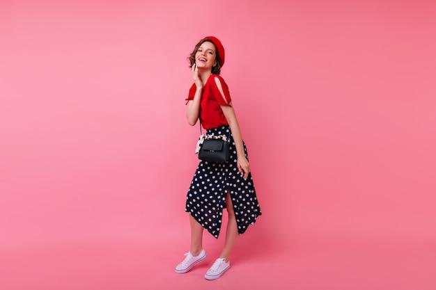 Pełnometrażowy portret entuzjastycznej francuskiej damy z uśmiechem. debonair krótkowłosa kobieta w długiej spódnicy, stojąca w pewnej pozie.