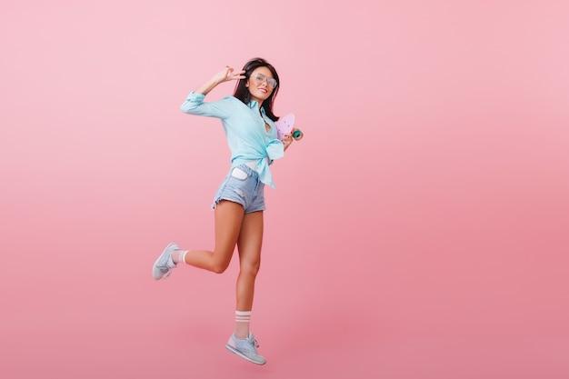 Pełnometrażowy portret inspirowanej ciemnowłosej kobiety w niebieskiej koszuli, skaczącej i śmiejącej się. cieszę się, że latynoska dziewczyna tańczy longboard ze znakiem pokoju.