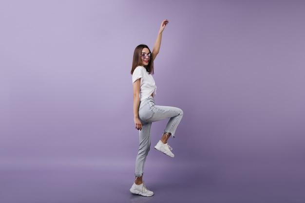 Pełnometrażowy portret inspirowanej modelki w jeansowych spodniach stojącej na jednej nodze. brunetka kobieta tańczy z przyjemnością.