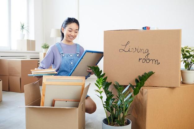 Pełnometrażowy portret młodej azjatki pakującej elementy wystroju do kartonów i uśmiechającej się szczęśliwie podekscytowana przeprowadzką do nowego domu lub akademika