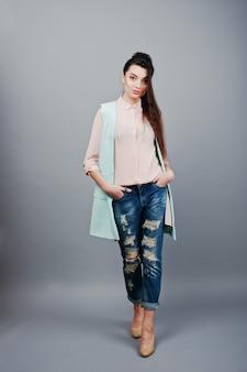 Pełnometrażowy portret młodej brunetki w różowej bluzce, turkusowej kurtce, zgranych dżinsach i kremowych butach