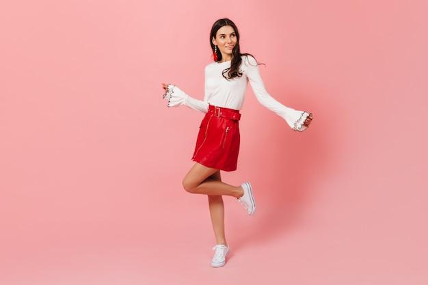 Pełnometrażowy portret młodej ciemnowłosej dziewczyny w skórzanej czerwonej spódnicy i lekkiej bluzce tańczącej na różowym tle.