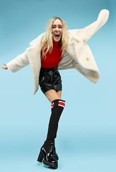 Pełnometrażowy portret młodej eleganckiej kobiety śmieszne blondynka w studio. koncepcja kobiecej mody i zakupów.
