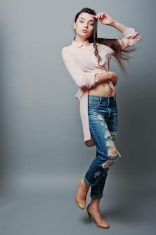 Pełnometrażowy portret młodej seksownej brunetki pokazującej pępek, ubrana w różową bluzkę, podarte dżinsy i kremowe buty