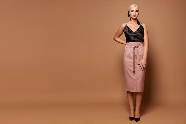 Pełnometrażowy portret modelki o idealnym ciele w czarnej bluzce i spódnicy midi na beżowym tle