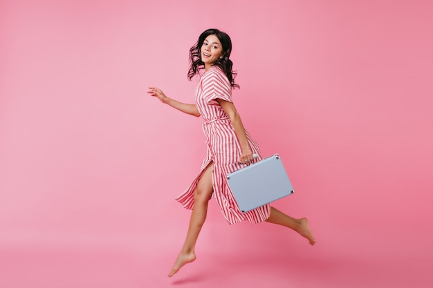 Pełnometrażowy portret pięknej kobiety w skoku. pani w pasiastym stroju szybko porusza się z bagażem.
