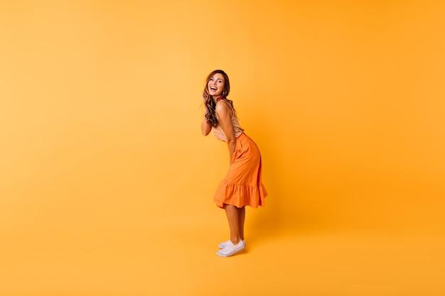 Pełnometrażowy portret pięknej kręconej dziewczyny w pomarańczowej spódnicy. studio portret pozytywnej pani tańczy na żółto.
