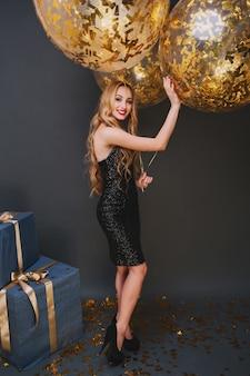 Pełnometrażowy portret radosnej europejskiej damy w czarnej sukni z balonami na imprezie. urocza blondynka urodzinowa dziewczyna nosi buty na wysokim obcasie stojąc na konfetti w pobliżu prezentów.