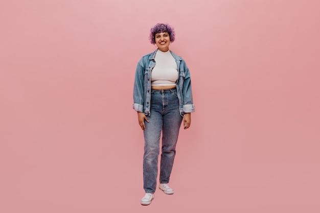 Pełnometrażowy portret radosnej kobiety z krótkimi fioletowymi włosami w dżinsowym garniturze, białych tenisówkach i lekkiej bluzce, uśmiechnięta