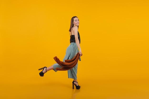 Pełnometrażowy portret roześmiany modelki w wysokich obcasach, zabawy. wewnętrzne zdjęcie szczupłej stylowej kobiety.