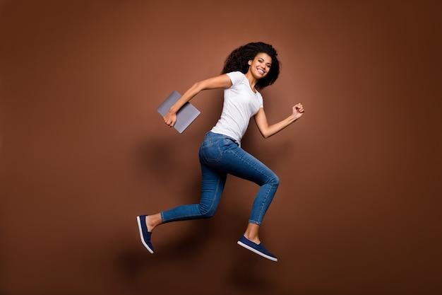 Pełnometrażowy portret śmiesznej ciemnoskórej pani skaczącej wysoko trzymającej zeszyt w pośpiechu lekcje uczennicy noszą dorywczo biały t-shirt dżinsy.