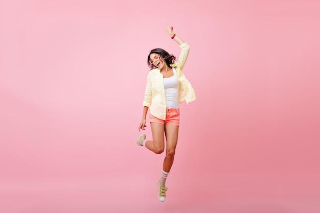 Pełnometrażowy portret szczupłej młodej kobiety z opaloną skórą, skaczący z uśmiechem. portret szczęśliwa brunetka dziewczyna w żółtej koszuli, taniec i śpiew z zamkniętymi oczami.