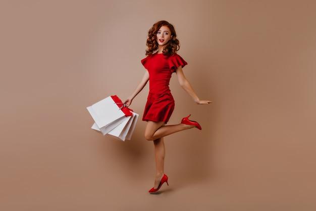 Pełnometrażowy portret szczupłej zakupoholiczki. zdziwiona długowłosa kobieta w czerwonej sukience, skoki.