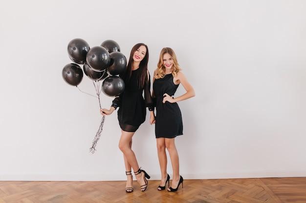 Pełnometrażowy portret szczupłych kobiet w czarnych sukienkach przygotowujących się do przyjęcia urodzinowego