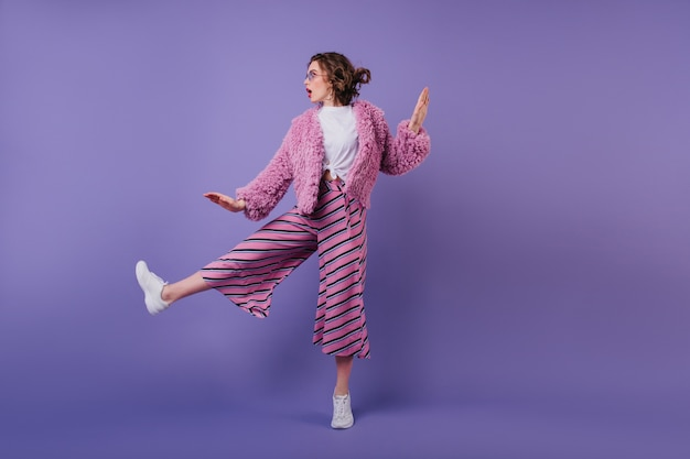 Pełnometrażowy portret uroczej kręconej kobiety tańczącej w pasiastych spodniach. modna brunetka dziewczyna skacze na fioletowej ścianie.