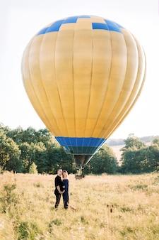 Pełnometrażowy portret uroczej młodej pary w czerni, przytulających się i cieszących się letnim spacerem po polu, czekając na ich wycieczkę balonem