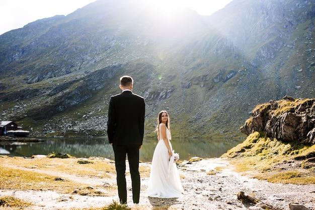 Pełnometrażowy portret uroczej panny młodej spoglądającej przez ramię na pana młodego, uśmiechającego się, gdy on patrzy na nią z ręką w kieszeniach w górach