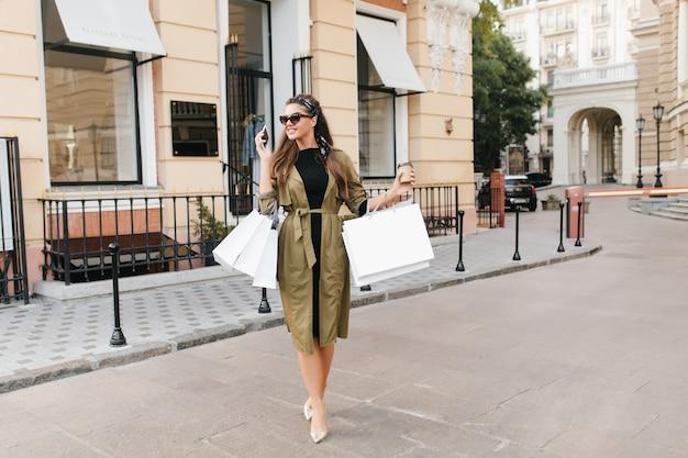 Pełnometrażowy portret uroczej szczupłej kobiety rozmawia przez telefon podczas weekendowych zakupów