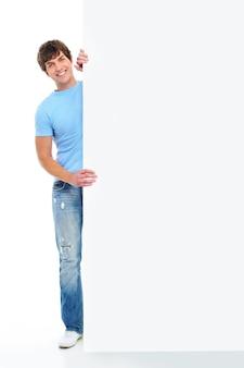 Pełnometrażowy portret uśmiechniętego młodego przystojnego mężczyzny z pustym sztandarem