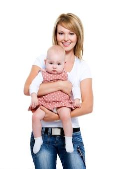 Pełnometrażowy portret uśmiechniętej matki z dzieckiem na rękach - na białym tle