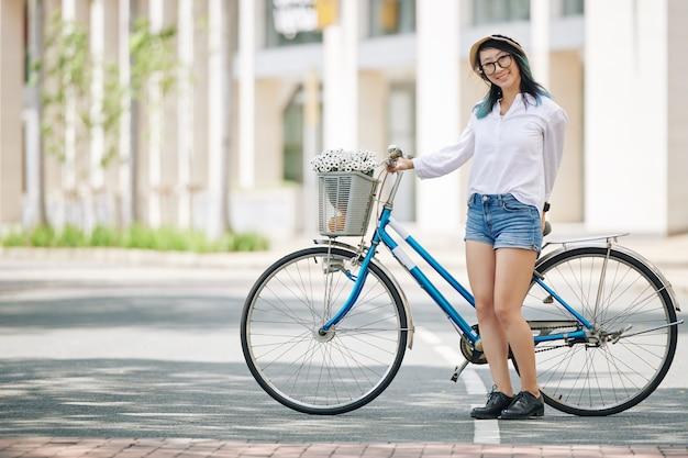 Pełnometrażowy portret wesoła ładna młoda kobieta w dżinsowych szortach, stojąc obok roweru i patrząc na kamery
