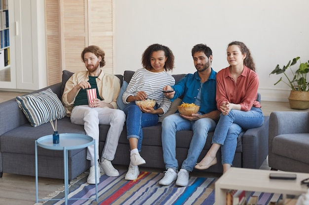 Pełnometrażowy portret wieloetnicznej grupy przyjaciół, którzy razem oglądają telewizję, siedząc na wygodnej kanapie w domu i delektując się przekąskami