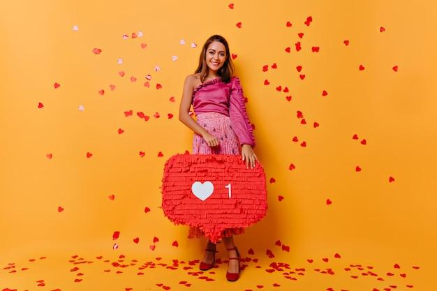 Pełnometrażowy portret zadowolonej blogerki uśmiechniętej na pomarańczowo. kryty portret rozmarzonej ciemnowłosej dziewczyny korzystającej z sieci społecznościowych.