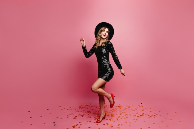 Pełnometrażowy portret zrelaksowanej, dobrze ubranej modelki. ładna europejska dziewczyna w czarnym kapeluszu tańczy z przyjemnością.