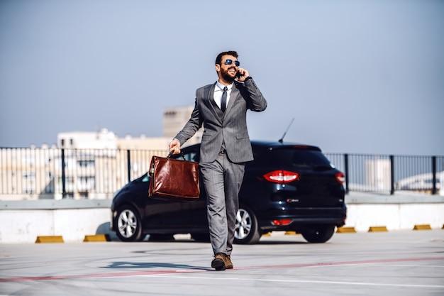 Pełnometrażowy przystojny biznesmen rasy kaukaskiej, brodaty, w garniturze i okularach przeciwsłonecznych, spaceruje po parkingu, rozmawia przez telefon i trzyma teczkę.