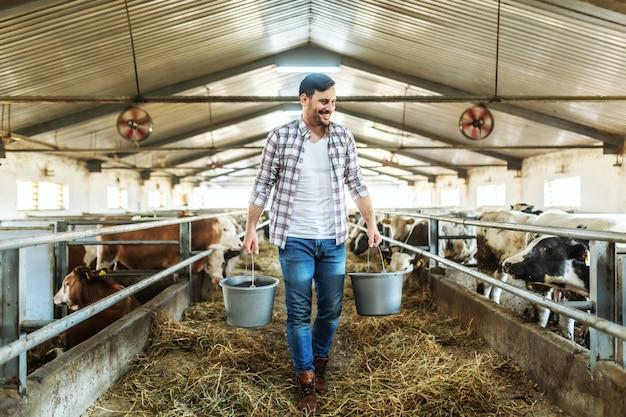 Pełnometrażowy przystojny rolnik kaukaski w kraciastej koszuli i dżinsach trzyma w rękach wiadra z karmą dla zwierząt. stabilne wnętrze.