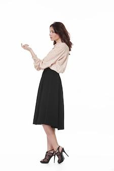 Pełnometrażowy wizerunek młodej brunetki z fryzurą w eleganckiej bluzce, czarnej spódnicy i wysokich obcasach