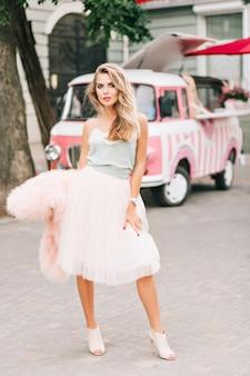 Pełnowymiarowa modelka w lekkiej tiulowej spódnicy z długimi blond włosami na tle samochodu retro. ona patrzy do kamery.