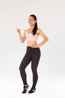 Pełnowymiarowa uśmiechnięta zadowolona atletka, azjatycka dziewczyna fitness w aktywnym stroju dokonująca wyboru, wskazująca i patrząc w lewy górny róg, wybierająca siłownię do treningu.