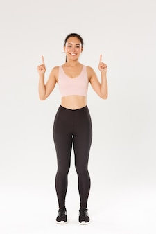 Pełnowymiarowa wesoła uśmiechnięta i urocza fitness dziewczyna, wskazująca palcami w górę, pokazująca reklamę sprzętu do ćwiczeń, kup członkostwo na trening.