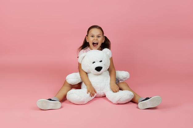 Pełnowymiarowa, zadowolona dziewczyna siedzi na podłodze z szeroko rozstawionymi nogami i trzyma białego misia
