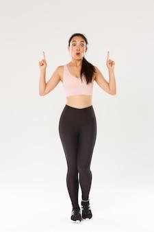 Pełnowymiarowa zdumiona i pod wrażeniem azjatycka atletka, sportsmenka w stroju sportowym, mówi wow i wskazuje palcami w górę, pokazując niesamowite zniżki na sprzęt do ćwiczeń.