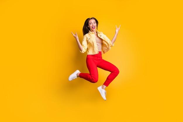 Pełnowymiarowe ciało zmieniło się w radosną, krzyczącą kobietę pokazującą rogate palce w czerwonych spodniach w białych butach na białym tle ściany w żywym kolorze