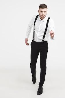 Pełnowymiarowe pionowe zdjęcie skoncentrowanego atrakcyjnego, nieogolonego mężczyzny w eleganckim garniturze na tle białej ściany studia, jego wygląd wyrażający determinację, powagę i pewność siebie