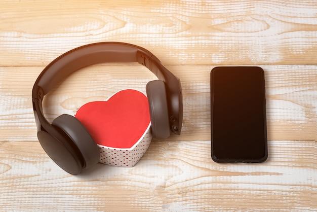 Pełnowymiarowe słuchawki bezprzewodowe naciągnięte na małe czerwone pudełko w kształcie serca i smartfon na jasnobrązowym drewnianym stole.