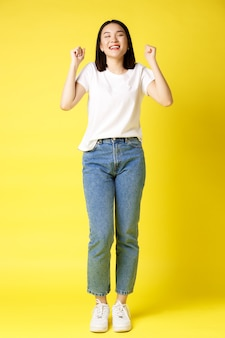 Pełnowymiarowe ujęcie wesołej azjatki w dżinsach i białej koszulce skaczącej ze szczęścia, wygrywającej nagrodę i radości, świętującej i krzyczącej z radością tak, na żółtym tle.