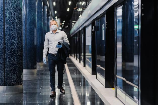Pełnowymiarowe ujęcie zamożnego biznesmena nosi oficjalne ubrania, maskę medyczną i rękawiczki, trzyma gazetę i smartfon, przestrzega zasad kwarantanny. pandemiczny wybuch koronawirusa, covid-19.