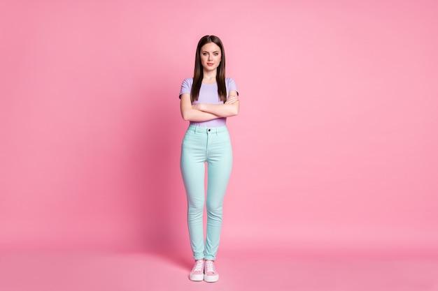 Pełnowymiarowe zdjęcie atrakcyjnej, chudej, biznesowej damy, w dobrym nastroju, z rękami skrzyżowanymi rękami, pewna siebie, nosić na co dzień fioletowy t-shirt turkusowe spodnie buty na białym tle różowy pastelowy kolor tła