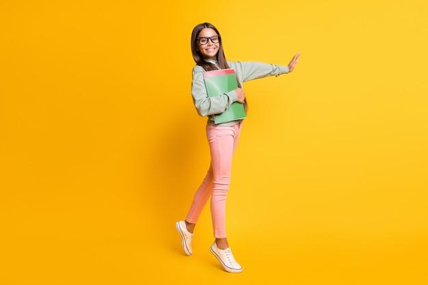 Pełnowymiarowe zdjęcie brunetki, która wraca do klasy, machając ręką na żółtym tle