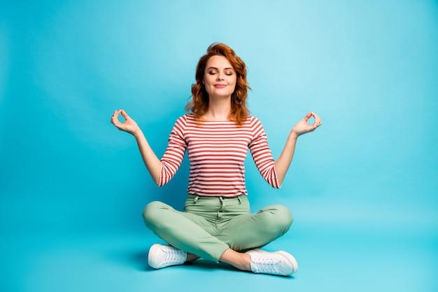 Pełnowymiarowe zdjęcie cichej, pogodnej kobiety siedzącej na podłodze ze skrzyżowanymi nogami pokaż znak om ćwiczenia joga medytacja nosić stylowy zielony strój odizolowany na niebieskim kolorze