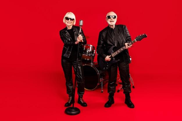 Pełnowymiarowe zdjęcie dwóch osób siwe włosy na emeryturze emeryt kobieta wokalista mężczyzna gitarzysta basowy cieszyć praktyka etap impreza wycieczka występ na białym tle nad jasnym połyskiem kolor tła