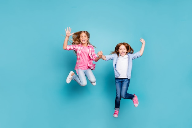 Pełnowymiarowe zdjęcie dwóch podekscytowanych, radosnych, optymistycznych dziewcząt w białych dżinsach, odizolowanych na niebieskim tle