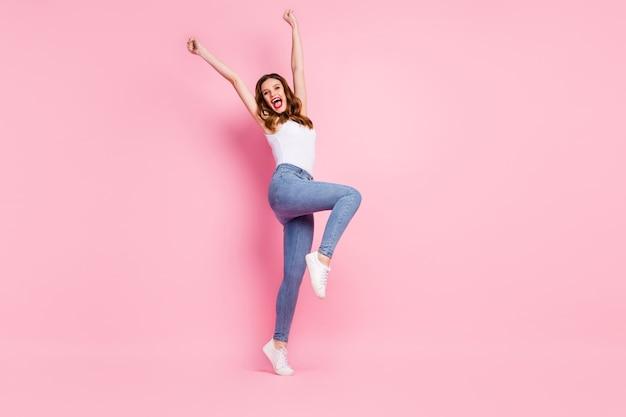 Pełnowymiarowe zdjęcie ekstatycznej wesołej dziewczyny unoszącej pięści z krzykiem