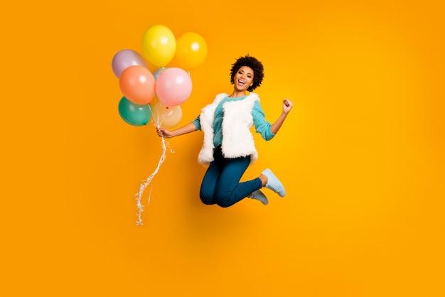 Pełnowymiarowe zdjęcie funky szalona afroamerykańska dziewczyna skok trzymaj balony wygrywaj wydarzenie krzyk tak podnieś pięści nosić białą turkusową stylowy modny sweter niebieskie spodnie spodnie izolowany jasny kolor ściana
