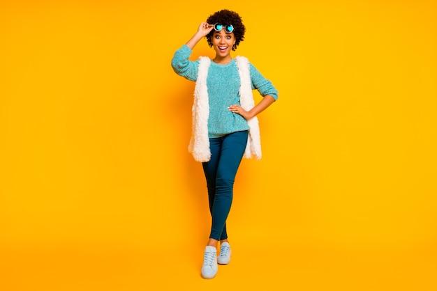 Pełnowymiarowe zdjęcie funky szalonej afroamerykanki dotknąć okulary przeciwsłoneczne usłyszeć jesień sprzedaż w czarny piątek pod wrażeniem krzyk nosić białe stylowe modne kamizelki niebieskie spodnie buty izolowane połysk kolor tło