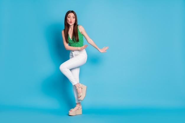 Pełnowymiarowe zdjęcie marzycielskiej dziewczyny tanecznej dyskoteki wyślij powietrze pocałunek nosić styl stylowy modny biały podkoszulek na białym tle nad niebieskim kolorem tła